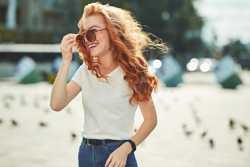 Όμορφο κοκκινομάλλες κορίτσι που έχει τη διασκέδαση στην οδό Τα κορίτσια έχουν έναν όμορφο αριθμό, μια άσπρη μπλούζα και τα τζιν  στοκ εικόνα