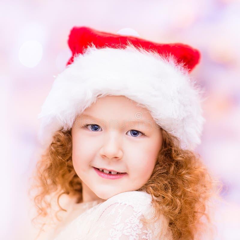 Όμορφο κοκκινομάλλες μικρό κορίτσι με τη μακριά σγουρή τρίχα που φορά το καπέλο Χριστουγέννων Άγιου Βασίλη στοκ εικόνα με δικαίωμα ελεύθερης χρήσης