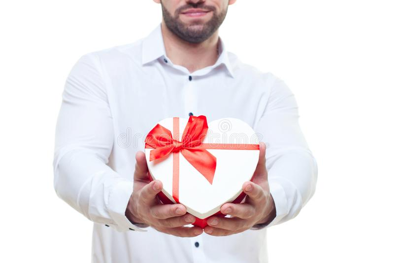 Όμορφο κομψό άτομο με το κιβώτιο δώρων βαλεντίνων με τα γυαλιά με μορφή της καρδιάς η ανασκόπηση απομόνωσε το λευκό στοκ εικόνες