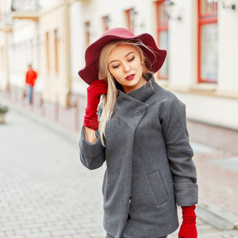 Όμορφο κομψό κορίτσι με το καπέλο μόδας και γκρίζο παλτό με στοκ εικόνες