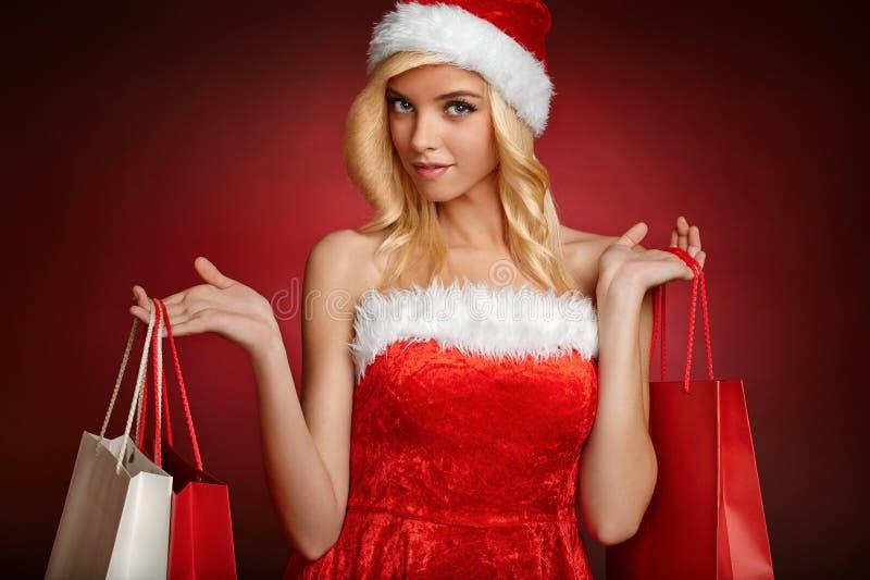Όμορφο κορίτσι Άγιου Βασίλη. Επιλογή τσαντών δώρων. στοκ φωτογραφία με δικαίωμα ελεύθερης χρήσης