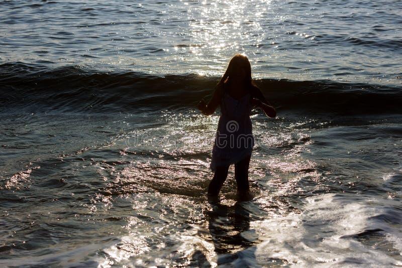 Όμορφο κορίτσι ή όμορφο ευτυχές μαγιό μικρών κοριτσιών που τρέχει στην αμμώδη παραλία κατά μήκος της θάλασσας ή της ωκεάνιας ακτή στοκ εικόνα με δικαίωμα ελεύθερης χρήσης