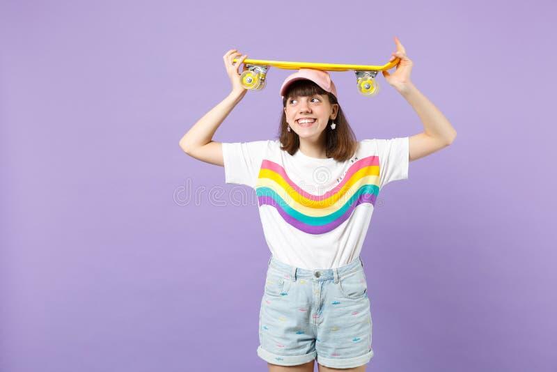 Όμορφο κορίτσι εφήβων στα ζωηρά ενδύματα που κρατά κίτρινο skateboard στο κεφάλι, που φαίνεται κατά μέρος απομονωμένο στον ιώδη τ στοκ φωτογραφίες με δικαίωμα ελεύθερης χρήσης
