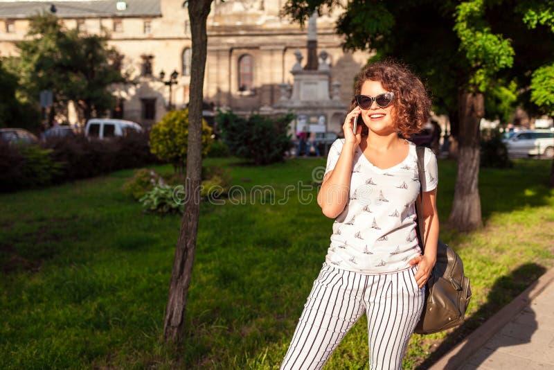 Όμορφο κορίτσι κολλεγίων που μιλά στο τηλέφωνο στο θερινό πάρκο Νέα γυναίκα που περπατά στην οδό πόλεων στοκ εικόνες