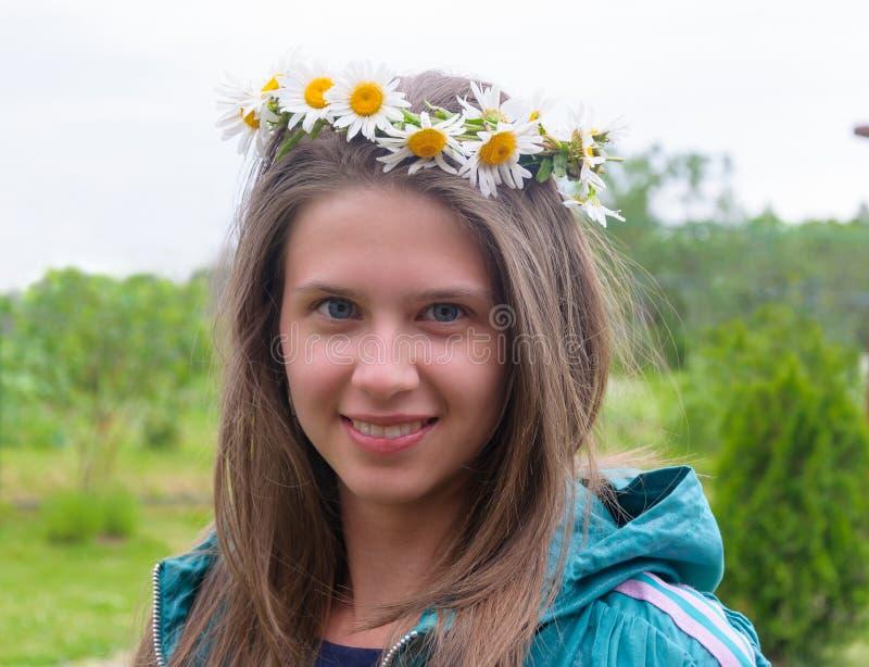 Όμορφο κορίτσι με ένα στεφάνι των μαργαριτών στο κεφάλι της στοκ εικόνα με δικαίωμα ελεύθερης χρήσης