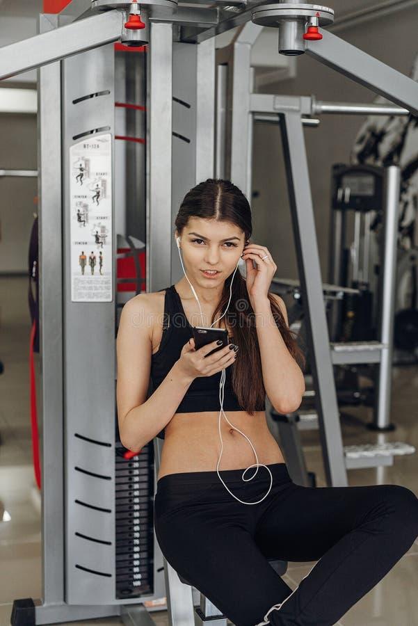 Όμορφο κορίτσι με ένα τηλέφωνο στη γυμναστική στοκ φωτογραφία με δικαίωμα ελεύθερης χρήσης