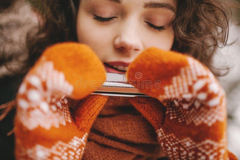 Όμορφο κορίτσι με κλειστή τη μάτια φυσαρμόνικα παιχνιδιού στα χειμερινά γάντια στοκ εικόνες