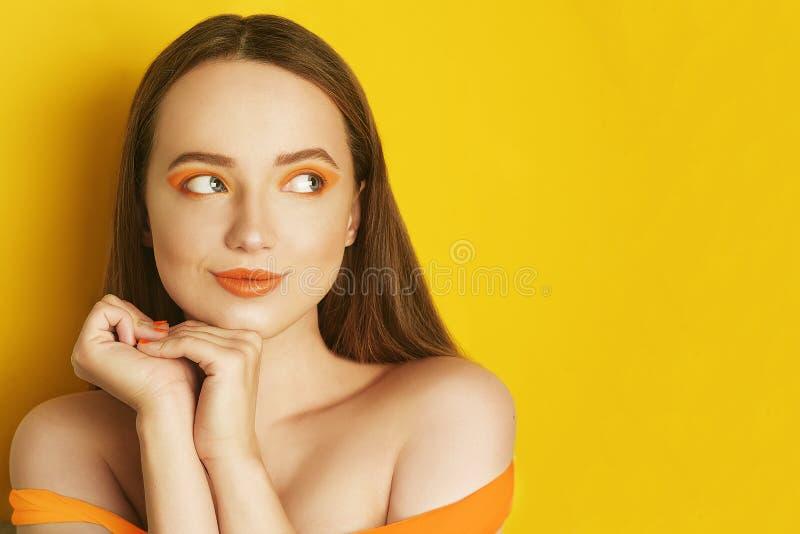 Όμορφο κορίτσι με λαμπρό καφετή ευθύ μακρυμάλλη Γυναίκα με το πορτοκάλι makeup με τις φακίδες Το κορίτσι κοντά στο κενό διάστημα  στοκ εικόνες