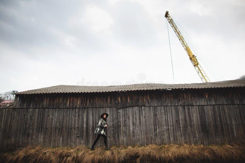 Όμορφο κορίτσι με μακρυμάλλη και μαύρο καπέλο, στάσεις στο υπόβαθρο του εκλεκτής ποιότητας παλαιού ξύλινου σπιτιού στοκ εικόνα