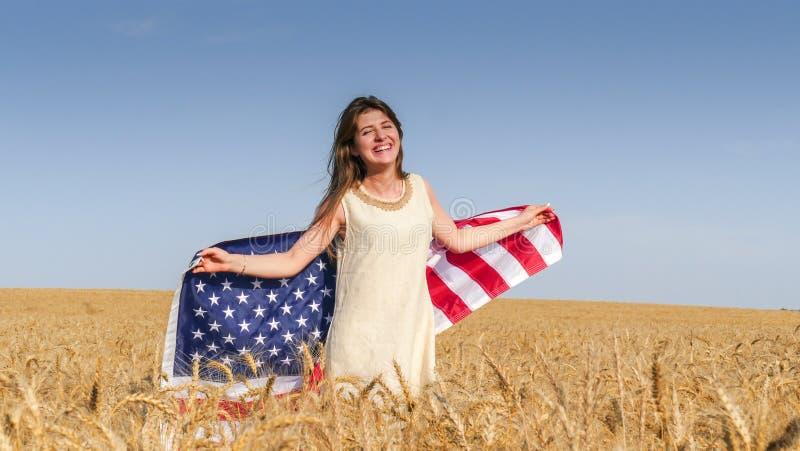 Όμορφο κορίτσι με μια αμερικανική σημαία στον τομέα στοκ φωτογραφίες