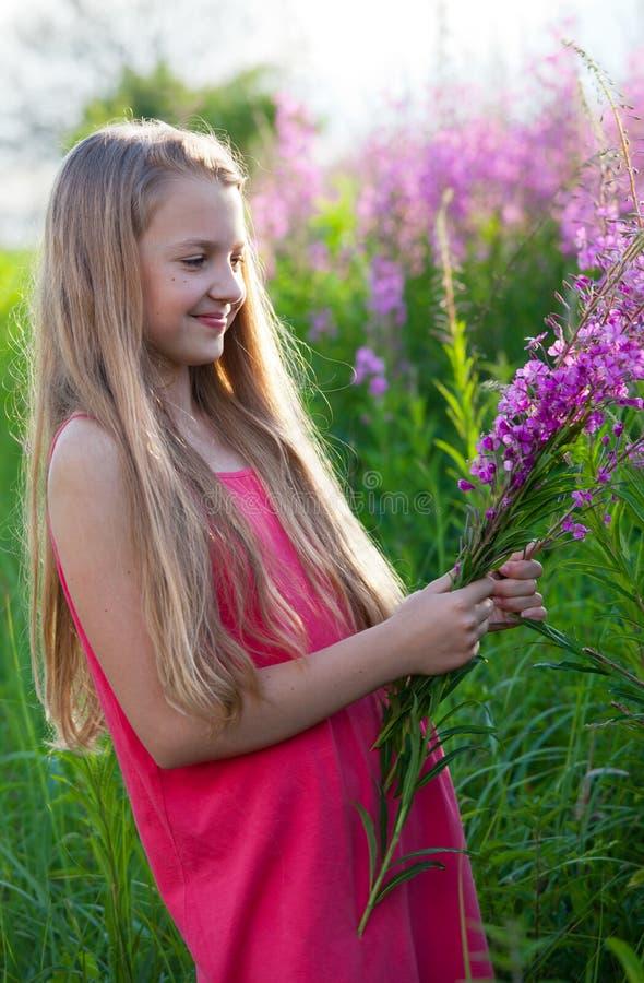 Όμορφο κορίτσι με τα λουλούδια στοκ εικόνα με δικαίωμα ελεύθερης χρήσης