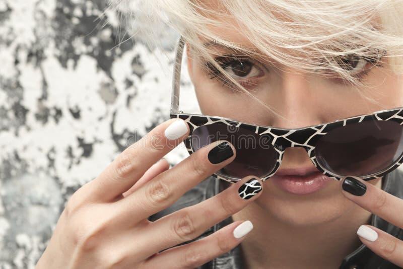 Όμορφο κορίτσι με τα ξανθά μαλλιά και το μαύρο άσπρο σχέδιο καρφιών στοκ εικόνες