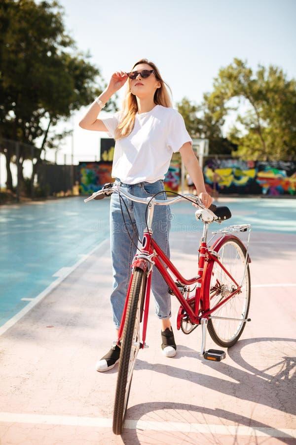 Όμορφο κορίτσι με τα ξανθά μαλλιά στα γυαλιά ηλίου που στέκονται με το κόκκινο κλασικό ποδήλατο στο γήπεδο μπάσκετ στο πάρκο Νέα  στοκ εικόνα με δικαίωμα ελεύθερης χρήσης