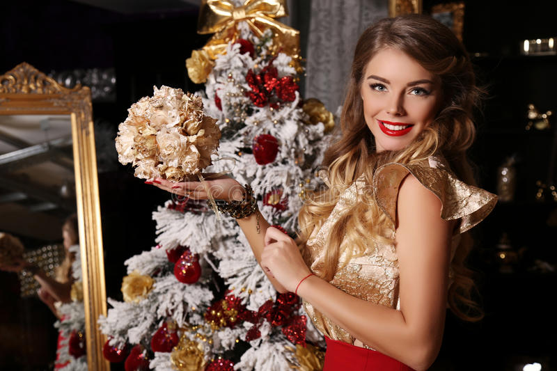 Όμορφο κορίτσι με τα ξανθά μαλλιά, που θέτουν εκτός από το χριστουγεννιάτικο δέντρο στοκ φωτογραφίες