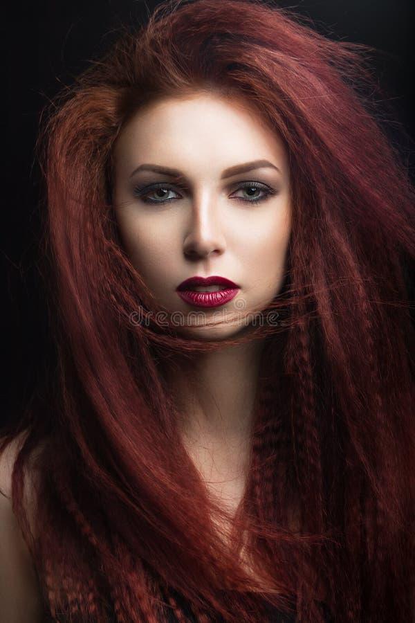 Όμορφο κορίτσι με τα φωτεινά χείλια makeup και burgundy με τον αέρα στην τρίχα Πρόσωπο ομορφιάς στοκ εικόνα