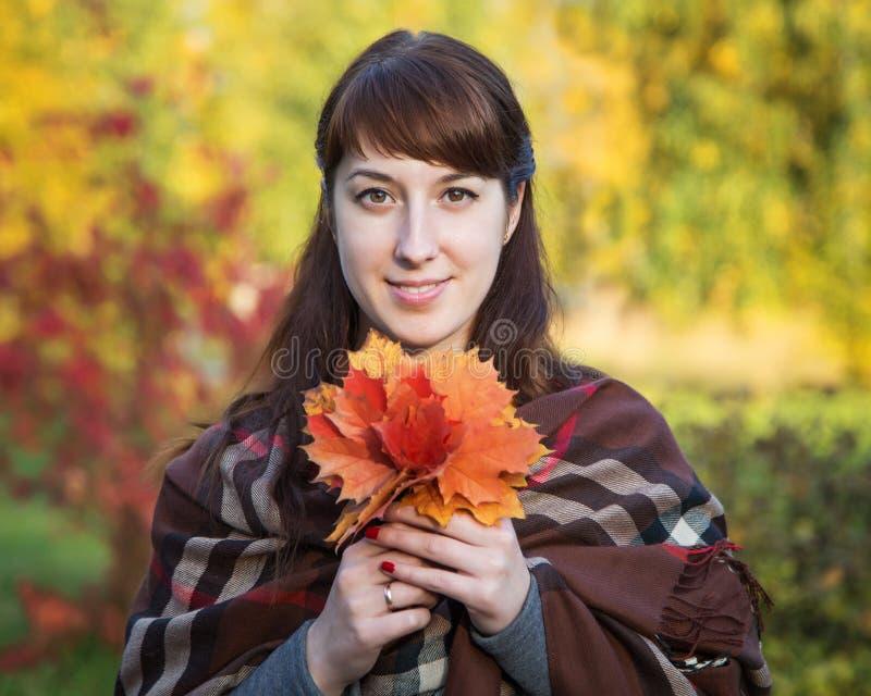 Όμορφο κορίτσι με τα φύλλα σφενδάμου στα χέρια στοκ φωτογραφία με δικαίωμα ελεύθερης χρήσης