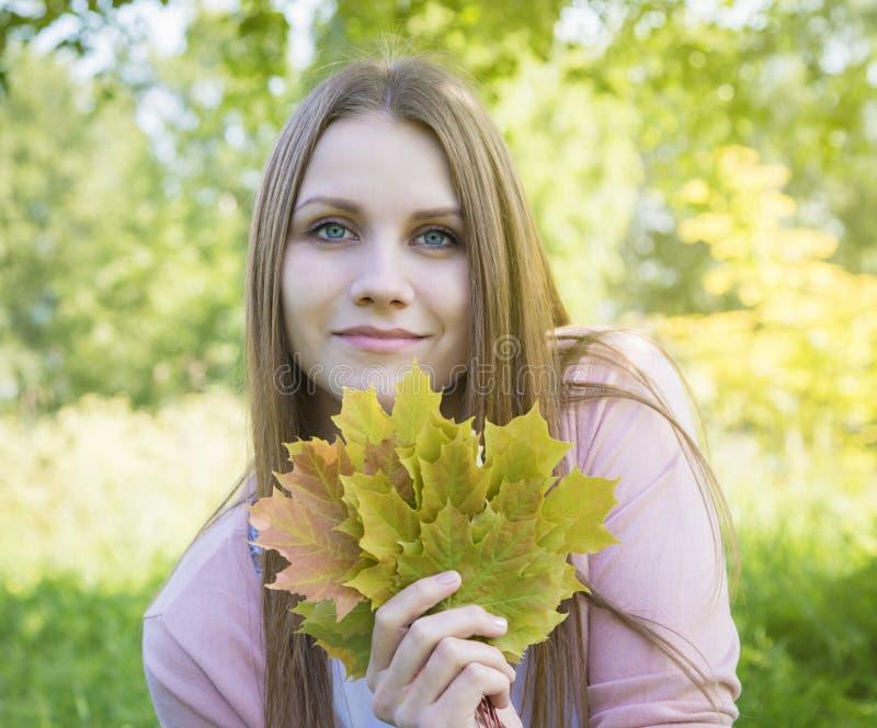 Όμορφο κορίτσι με τα φύλλα σφενδάμου στοκ εικόνα με δικαίωμα ελεύθερης χρήσης