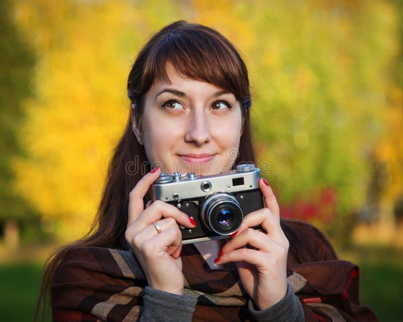 Όμορφο κορίτσι με την αναδρομική κάμερα στο πάρκο φθινοπώρου στοκ φωτογραφία με δικαίωμα ελεύθερης χρήσης