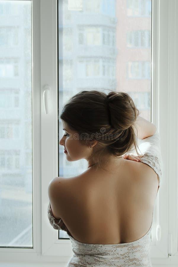 Όμορφο κορίτσι με τη μακριά καφετιά τρίχα σε ένα άσπρο φόρεμα που στέκεται στο παράθυρο από την πλάτη στοκ φωτογραφίες με δικαίωμα ελεύθερης χρήσης