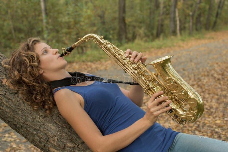 Όμορφο κορίτσι με τη σγουρή τρίχα που παίζει το saxophone στο χρυσό στοκ φωτογραφία