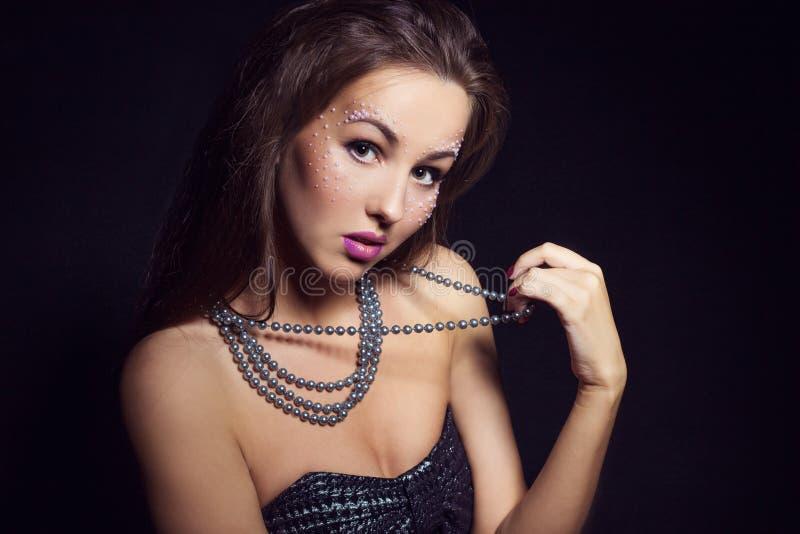 Όμορφο κορίτσι με τη σκοτεινή τρίχα και έξυπνο makeup με τις χάντρες διαθέσιμες στο στούντιο σε ένα μαύρο υπόβαθρο νέου έτους mak στοκ εικόνες
