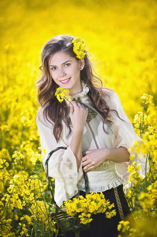 Όμορφο κορίτσι με το καλάθι που χαμογελά στον τομέα συναπόσπορων στοκ εικόνες με δικαίωμα ελεύθερης χρήσης