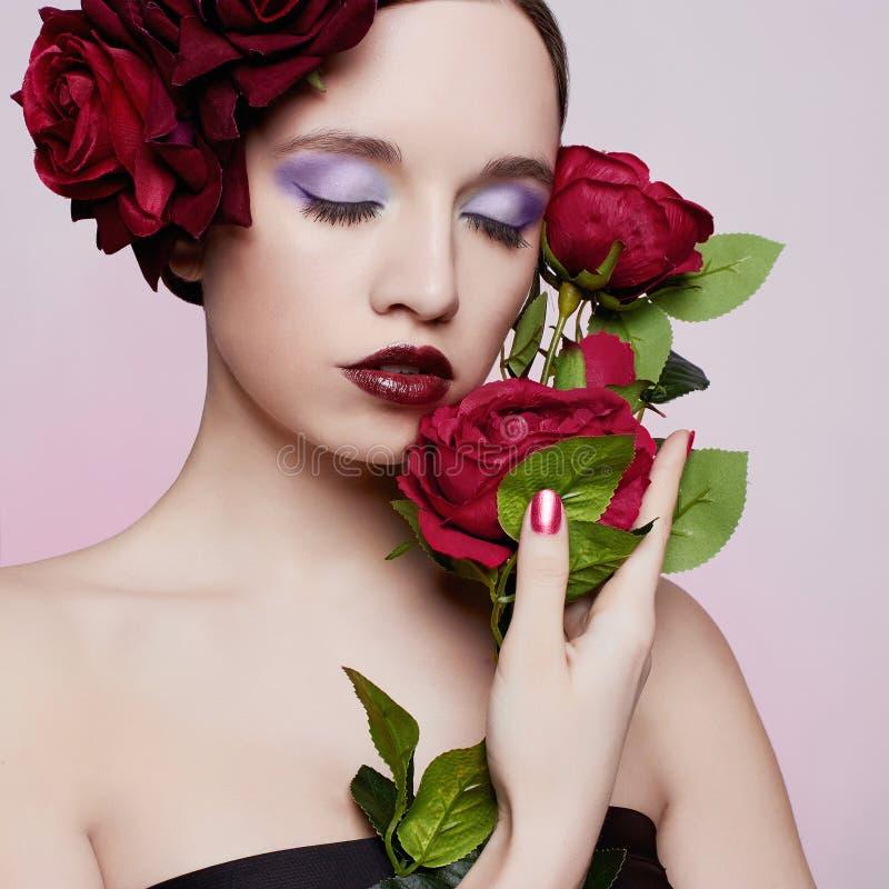 Όμορφο κορίτσι με το κόκκινο λουλούδι τριαντάφυλλων στοκ εικόνες