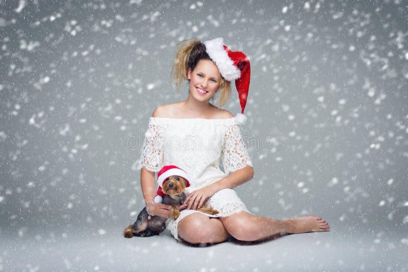 Όμορφο κορίτσι με το σκυλί yorkie στο santa ΚΑΠ στοκ εικόνα