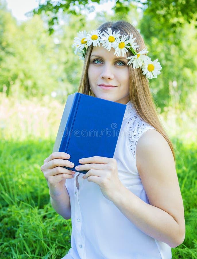 Όμορφο κορίτσι με το στεφάνι των μαργαριτών και ενός βιβλίου στοκ εικόνες