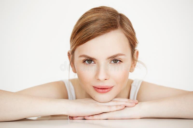 Όμορφο κορίτσι με το τέλειο καθαρό χαμόγελο δερμάτων που εξετάζει τη συνεδρίαση καμερών στον πίνακα πέρα από το άσπρο υπόβαθρο Be στοκ εικόνες με δικαίωμα ελεύθερης χρήσης