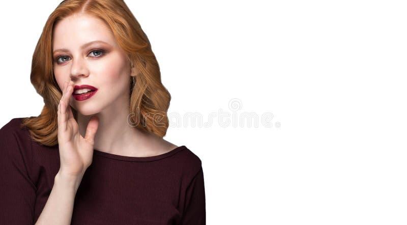 Όμορφο κορίτσι με το φωτεινό makeup και τη σγουρή τρίχα που λέει ένα μυστικό Νέα ευτυχής γυναίκα πορτρέτου που καλεί σε κάποιο στοκ φωτογραφία με δικαίωμα ελεύθερης χρήσης