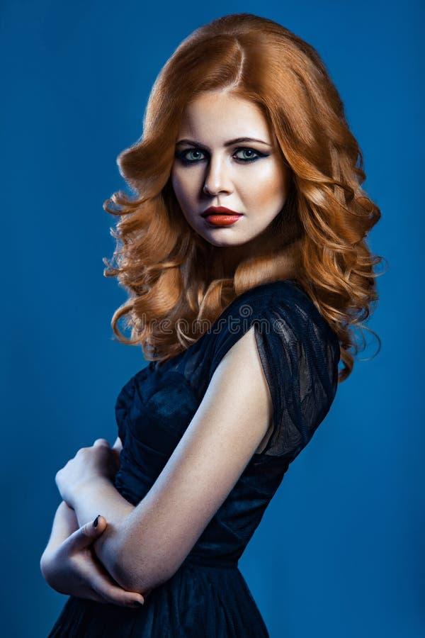 Όμορφο κορίτσι μόδας με τη μακριά κυματιστή κόκκινη καφετιά τρίχα ξανθομάλλες πρότυπο με το σγουρό hairstyle και το μοντέρνο καπν στοκ φωτογραφίες με δικαίωμα ελεύθερης χρήσης