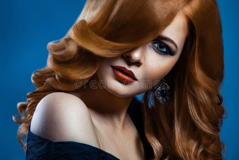 Όμορφο κορίτσι μόδας με τη μακριά κυματιστή κόκκινη καφετιά τρίχα ξανθομάλλες πρότυπο με το σγουρό hairstyle και το μοντέρνο καπν στοκ φωτογραφία