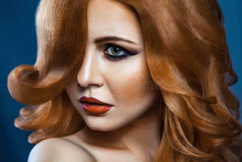 Όμορφο κορίτσι μόδας με τη μακριά κυματιστή κόκκινη καφετιά τρίχα ξανθομάλλες πρότυπο με το σγουρό hairstyle και το μοντέρνο καπν στοκ εικόνα με δικαίωμα ελεύθερης χρήσης