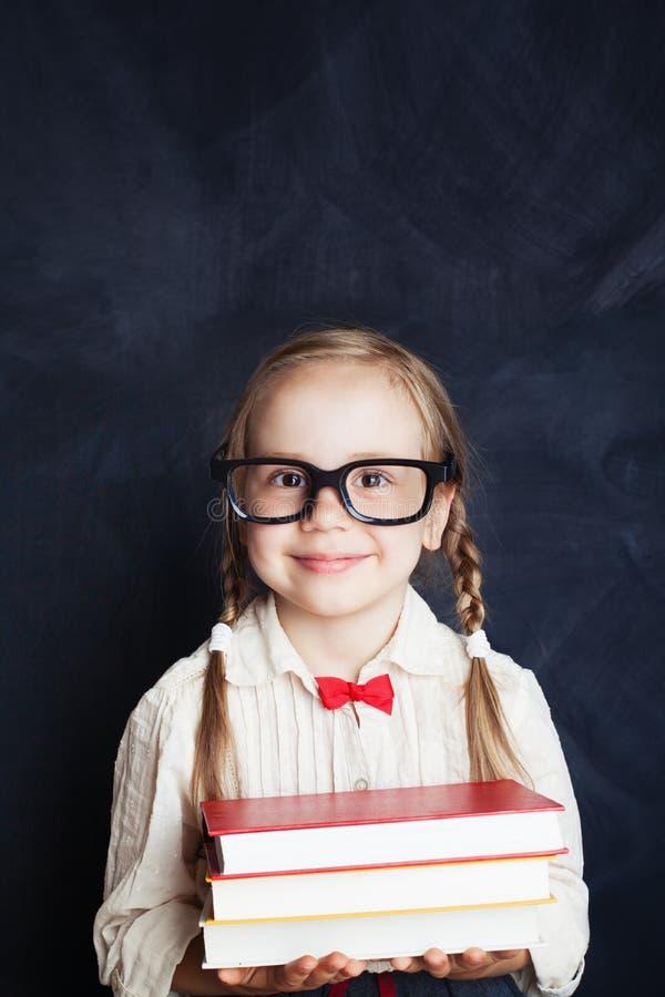 Όμορφο κορίτσι παιδιών με το σωρό των βιβλίων στο υπόβαθρο πινάκων κιμωλίας στοκ εικόνα