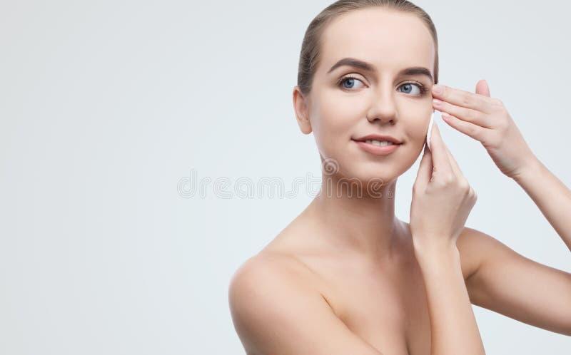 Όμορφο κορίτσι που αφαιρεί makeup από το πρόσωπό της με το μαξιλάρι βαμβακιού στοκ εικόνες