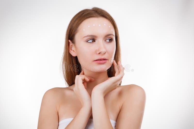 Όμορφο κορίτσι που βάζει την του προσώπου κρέμα ή τη μάσκα στο νέο δέρμα προσώπου στοκ εικόνες με δικαίωμα ελεύθερης χρήσης