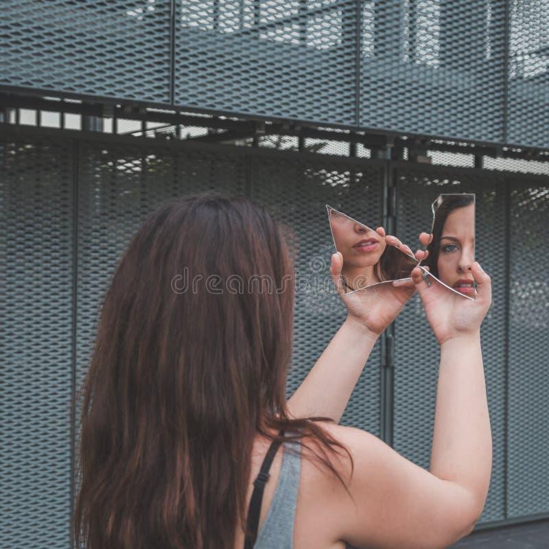 Όμορφο κορίτσι που εξετάζει την σε έναν σπασμένο καθρέφτη στοκ φωτογραφίες