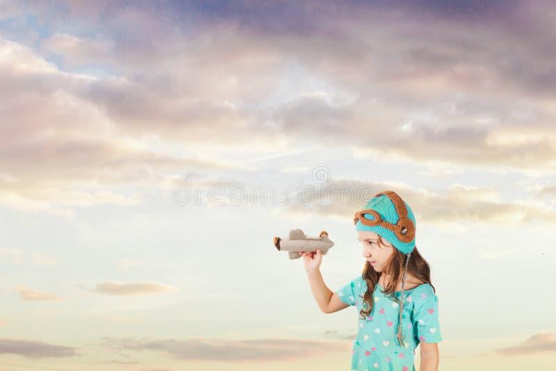 Όμορφο κορίτσι που εξετάζει το αεροπλάνο παιχνιδιών στα όπλα της στοκ εικόνα με δικαίωμα ελεύθερης χρήσης
