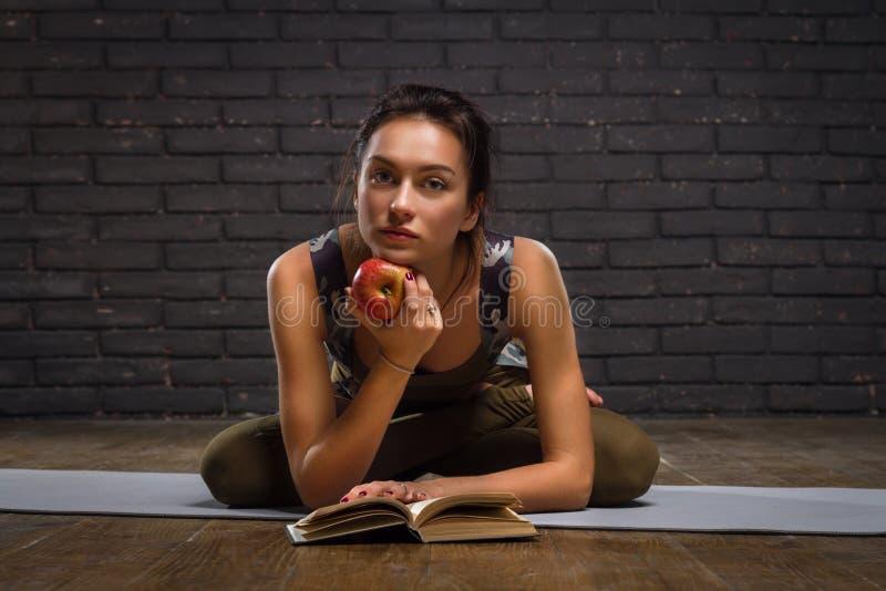Όμορφο κορίτσι που κάνει τις ασκήσεις γιόγκας και το διαβασμένο βιβλίο στοκ εικόνα με δικαίωμα ελεύθερης χρήσης