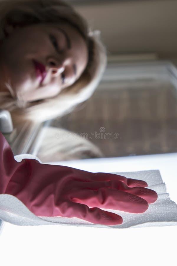Όμορφο κορίτσι που κάνει τον υγρό καθαρισμό και το σκούπισμα με ηλεκτρική σκούπα στοκ φωτογραφίες