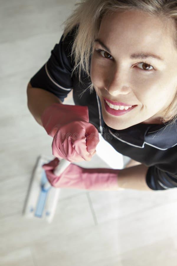 Όμορφο κορίτσι που κάνει τον υγρό καθαρισμό και το σκούπισμα με ηλεκτρική σκούπα στοκ φωτογραφία με δικαίωμα ελεύθερης χρήσης