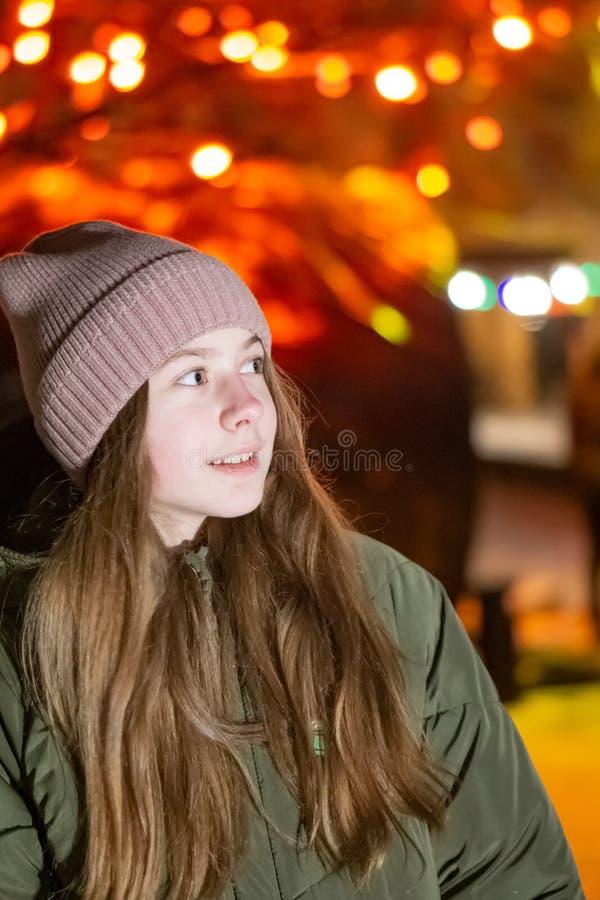 Όμορφο κορίτσι που κοιτάζει κάτω στην οδό πόλεων νύχτας ενάντια στο σκηνικό της πυράκτωσης storefront Υπόβαθρο με το bokeh διάστη στοκ εικόνα