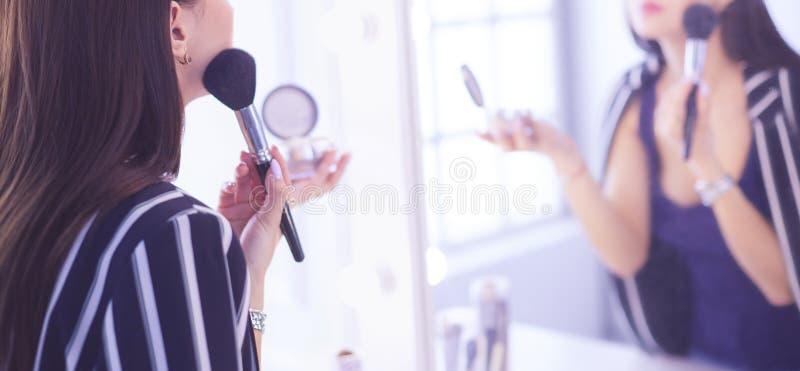 Όμορφο κορίτσι που κοιτάζει στον καθρέφτη και που εφαρμόζει το καλλυντικό με μια μεγάλη βούρτσα στοκ εικόνα