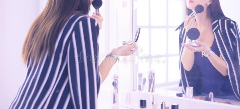 Όμορφο κορίτσι που κοιτάζει στον καθρέφτη και που εφαρμόζει το καλλυντικό με μια μεγάλη βούρτσα στοκ εικόνα με δικαίωμα ελεύθερης χρήσης