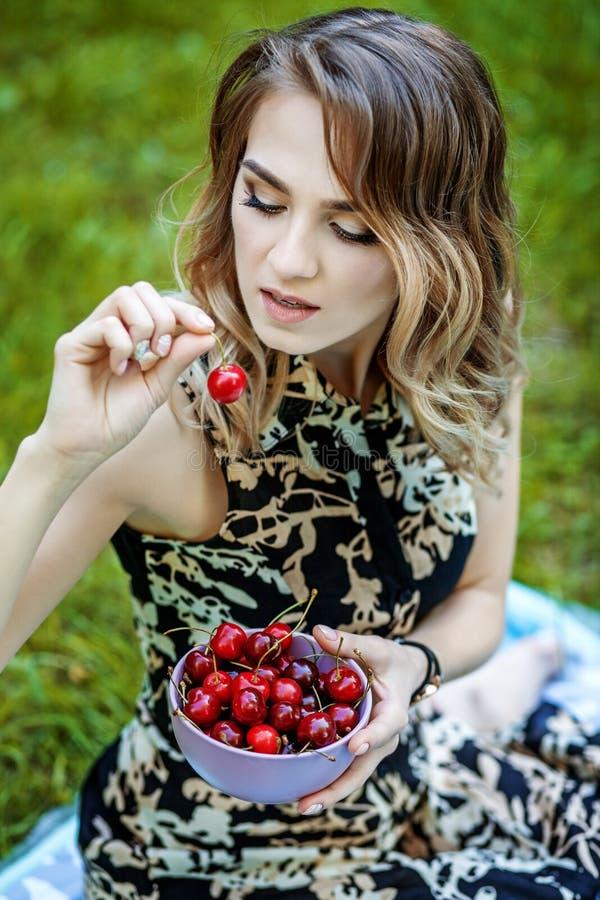 Όμορφο κορίτσι που κρατά ένα κύπελλο των κερασιών καυτό καλοκαίρι Το conce στοκ εικόνα