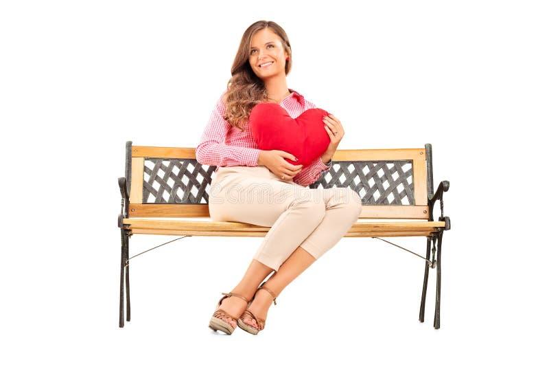 Όμορφο κορίτσι που κρατά μια κόκκινη καρδιά καθισμένη στον πάγκο στοκ εικόνα