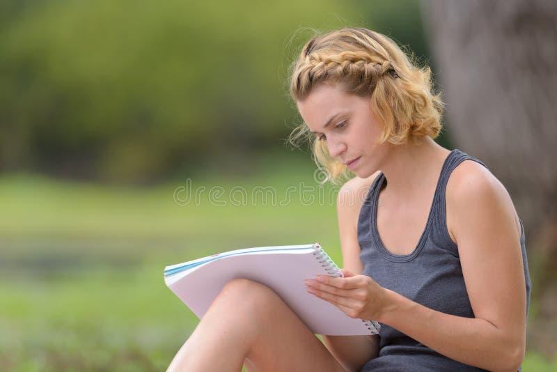 Όμορφο κορίτσι που κρατά το ανοικτό βιβλίο και που διαβάζει στο πάρκο στοκ φωτογραφία με δικαίωμα ελεύθερης χρήσης