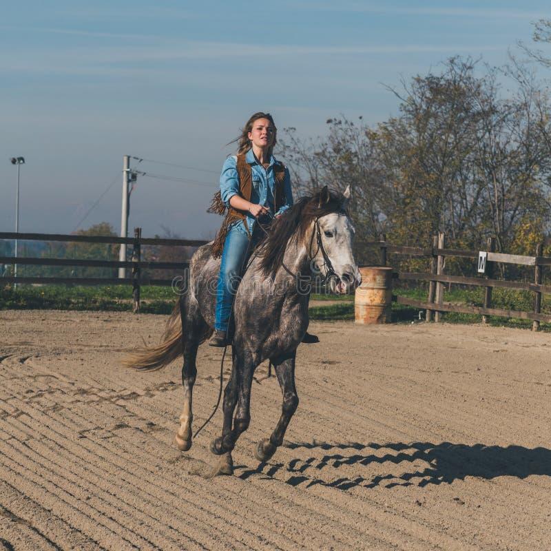 Όμορφο κορίτσι που οδηγά το γκρίζο άλογό της στοκ φωτογραφίες