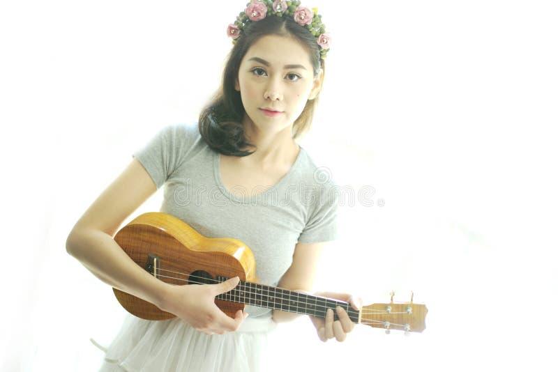 Όμορφο κορίτσι που παίζει ukulele στοκ φωτογραφίες